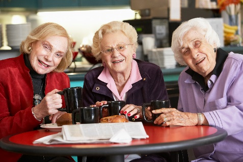 Three ladies at a table with mugs